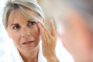 aging woman looking at her reflection and wrinkles