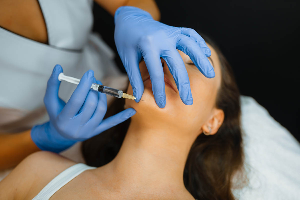 woman getting injection in chin for double chin treatment
