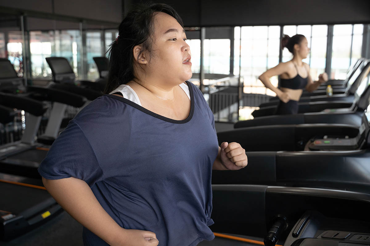 obese woman running on a treadmill at gym.